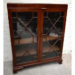 An early 20th century mahogany bookcase, the pair of astragal glazed doors, enclosing an arrangement