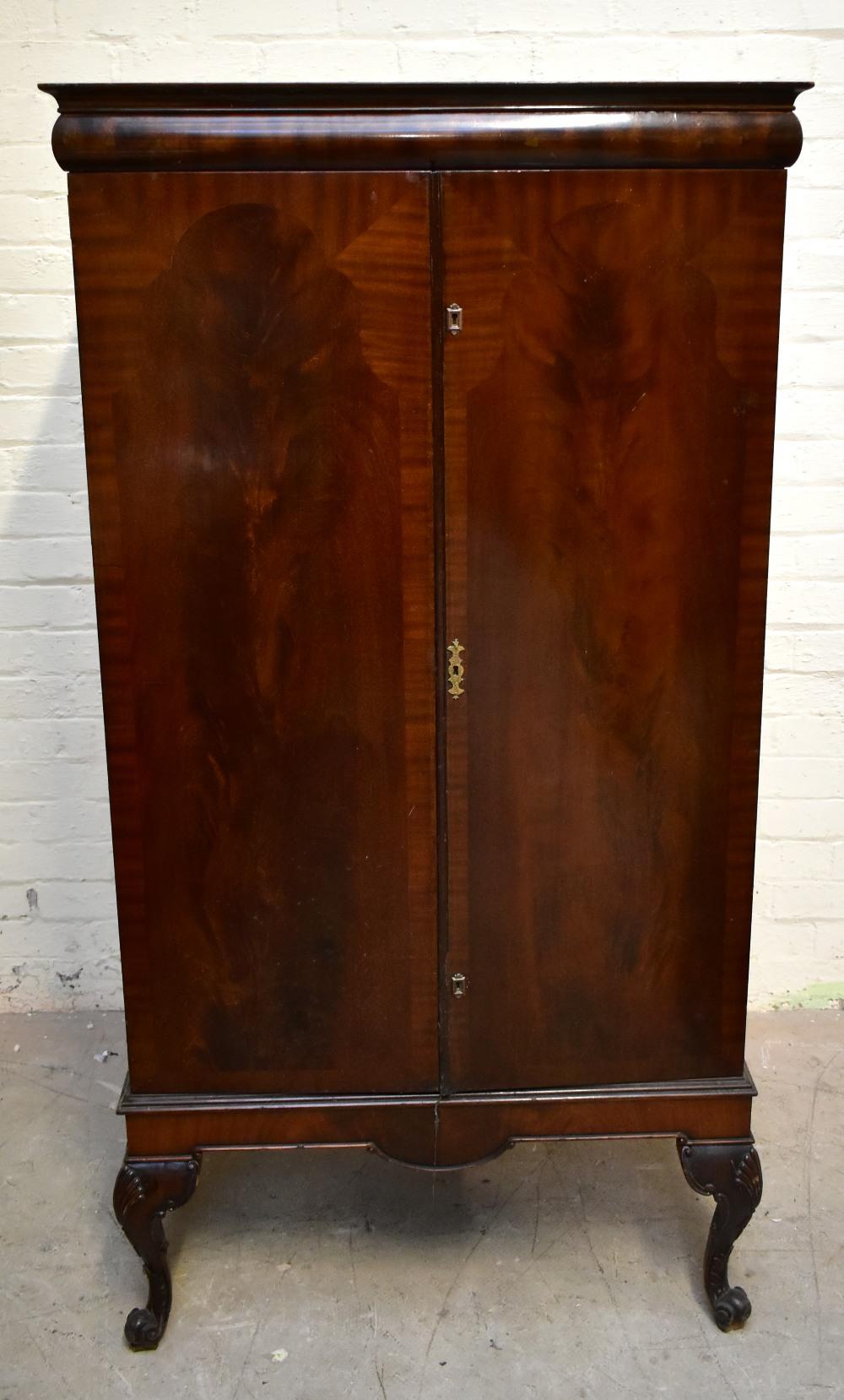 A 1950s mahogany veneered twin door silver cabinet, the twin panelled doors enclosing seven