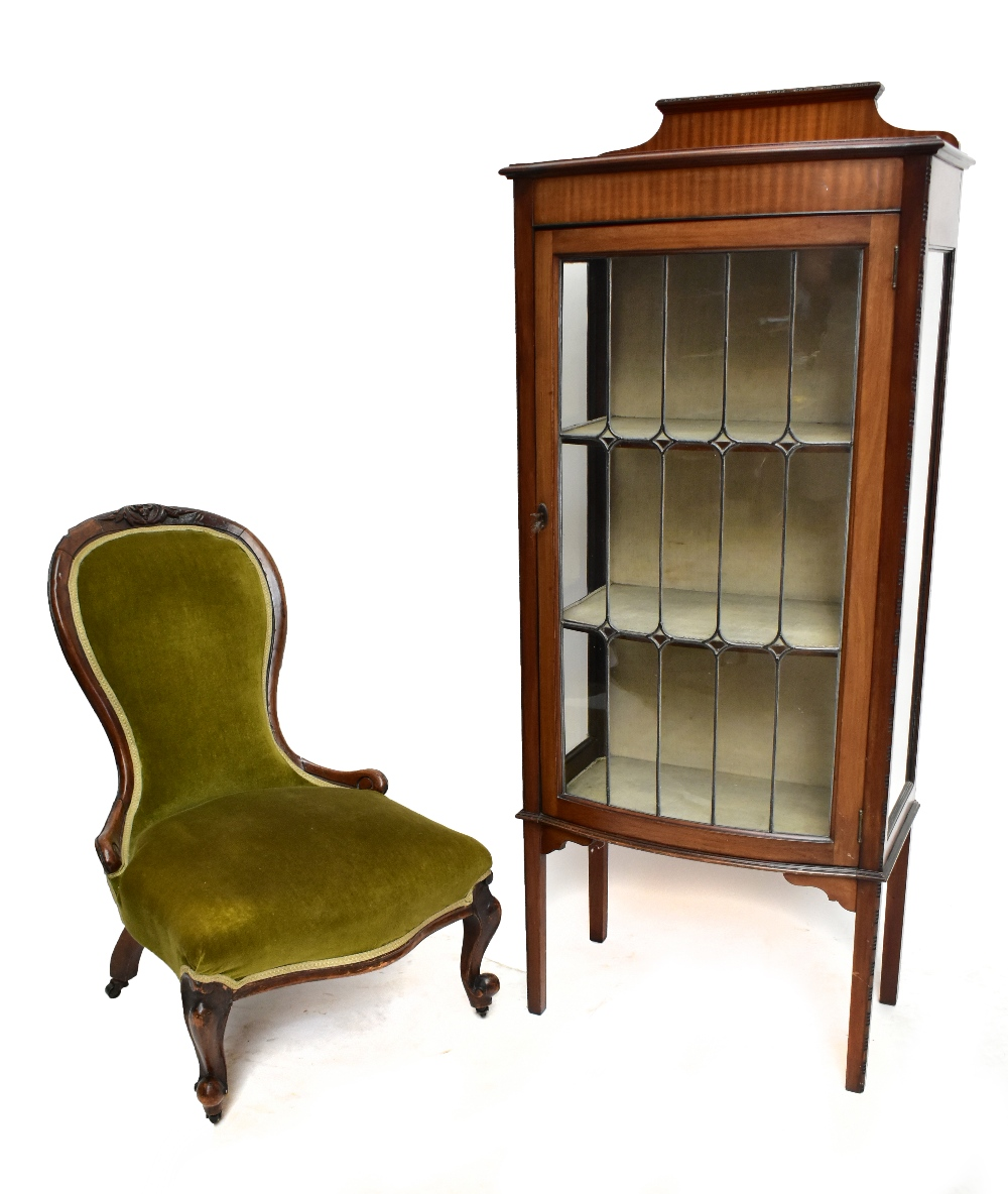 An early 20th century mahogany bow front display cabinet, the leaded glazed door enclosing two