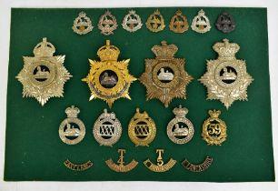 EAST LANCASHIRE REGIMENT; a good group of badges including four helmet/shako plates, one gilt with