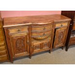 A carved walnut sideboard, with two bow front drawers above a small double panelled cupboard door,