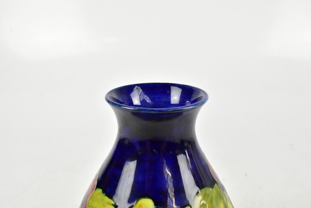 WALTER MOORCROFT; a baluster shaped vase decorated in the Hibiscus pattern on a blue ground, - Image 3 of 4