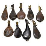Nine 19th century leather powder flasks, seven with brass mounts, none visibly signed (9).