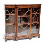 A late 19th century breakfront bookcase, the three astragal glazed doors enclosing adjustable