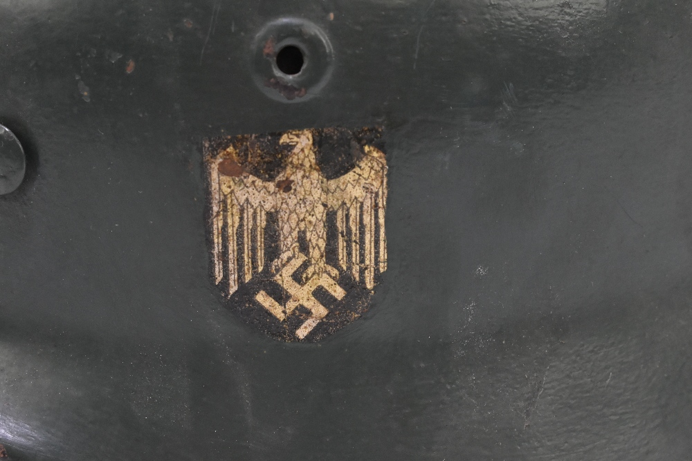 A German WWII Wehrmacht helmet bearing eagle and swastika decal, retaining leather liner and - Image 2 of 6