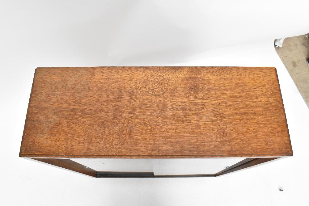 An oak bookcase with three sliding glass doors on castors, height 91cm, width 91.5cm, depth 22cm, - Image 5 of 6