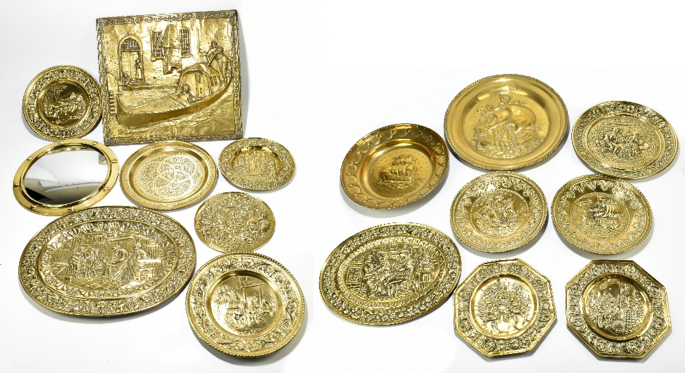 A collection of thirteen early 20th century embossed brass wall plates and chargers, probably Dutch,