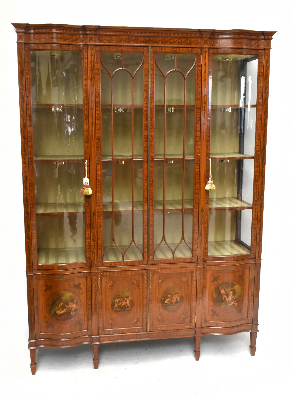 A fine late Victorian satinwood painted display cabinet with moulded cornice, serpentine side glazed