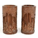 A pair of Chinese carved bamboo brush pots of cylindrical form, carved with elders in landscape