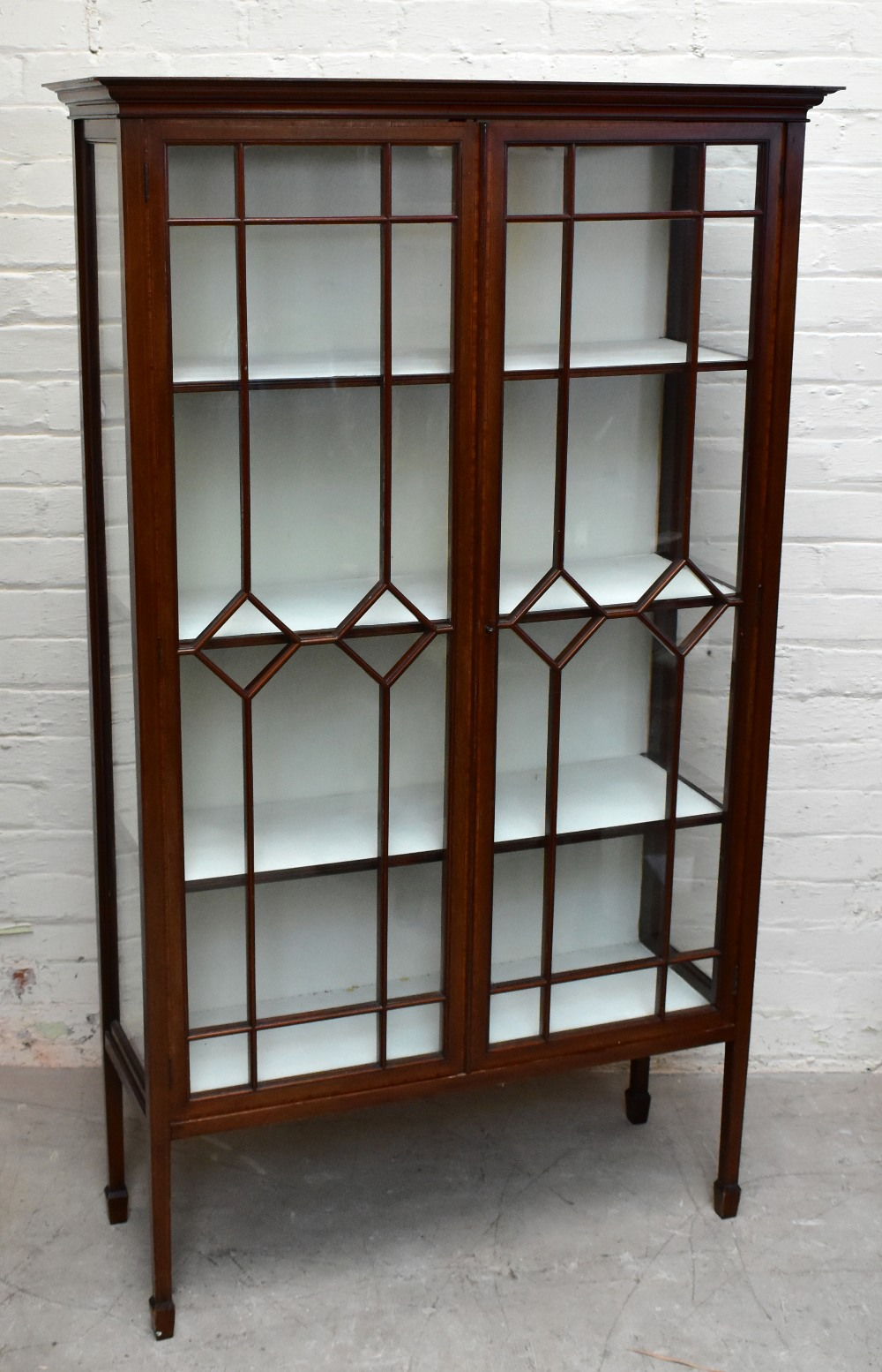AnEdwardian inlaidmahogany display cabinet, with two astragal glazed doors enclosing glass