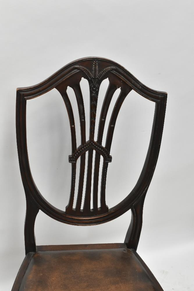 A set of four early 20th century mahogany shield back dining chairs with carved weatsheaf detail, - Image 3 of 3