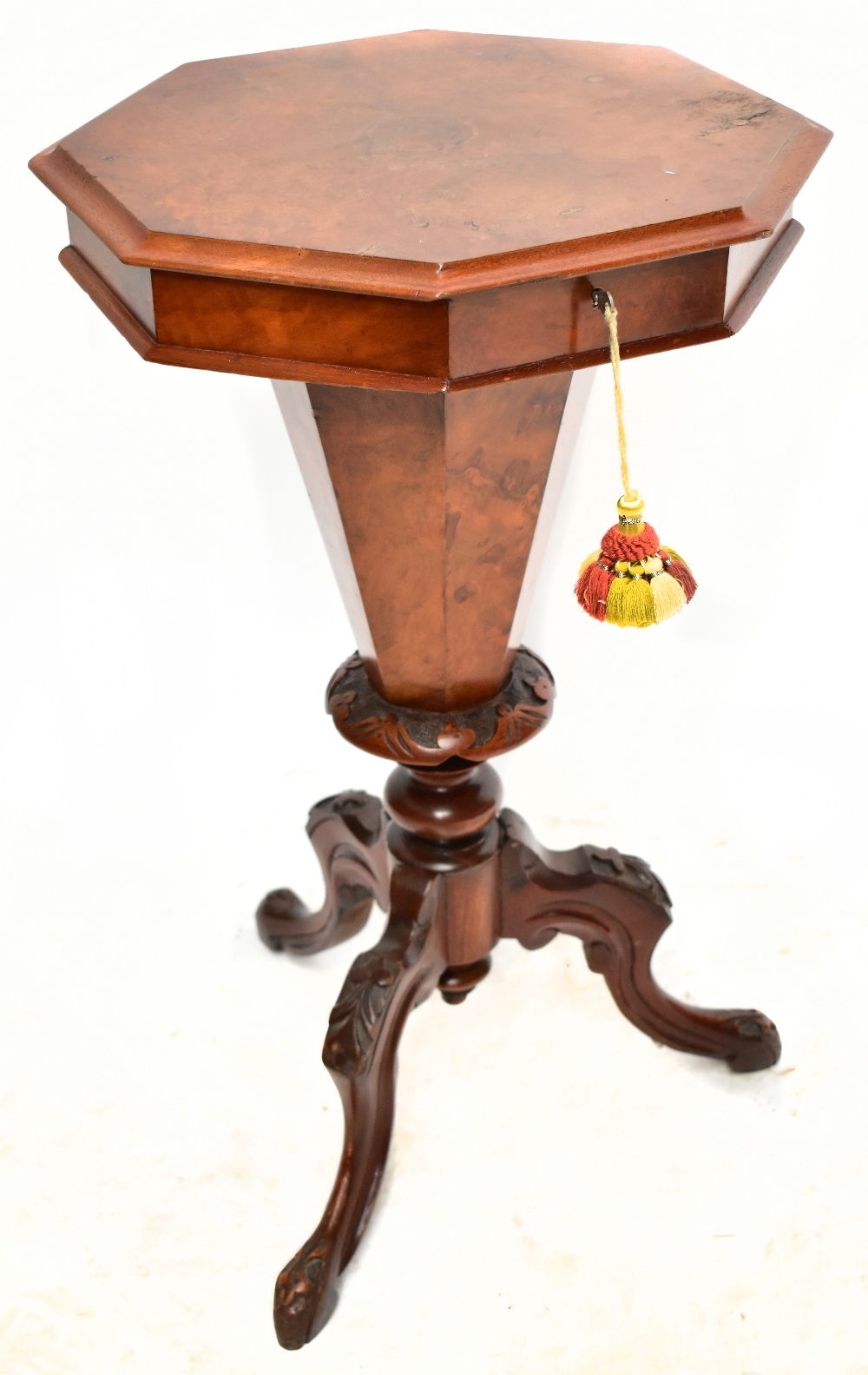 A Victorian walnut octagonal sewing table with fitted interior on three knee carved outswept