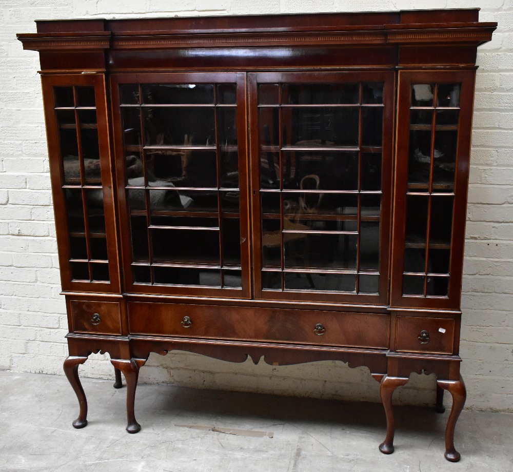 An early 20th century inlaid mahogany inverted breakfront display cabinet, the four astragal