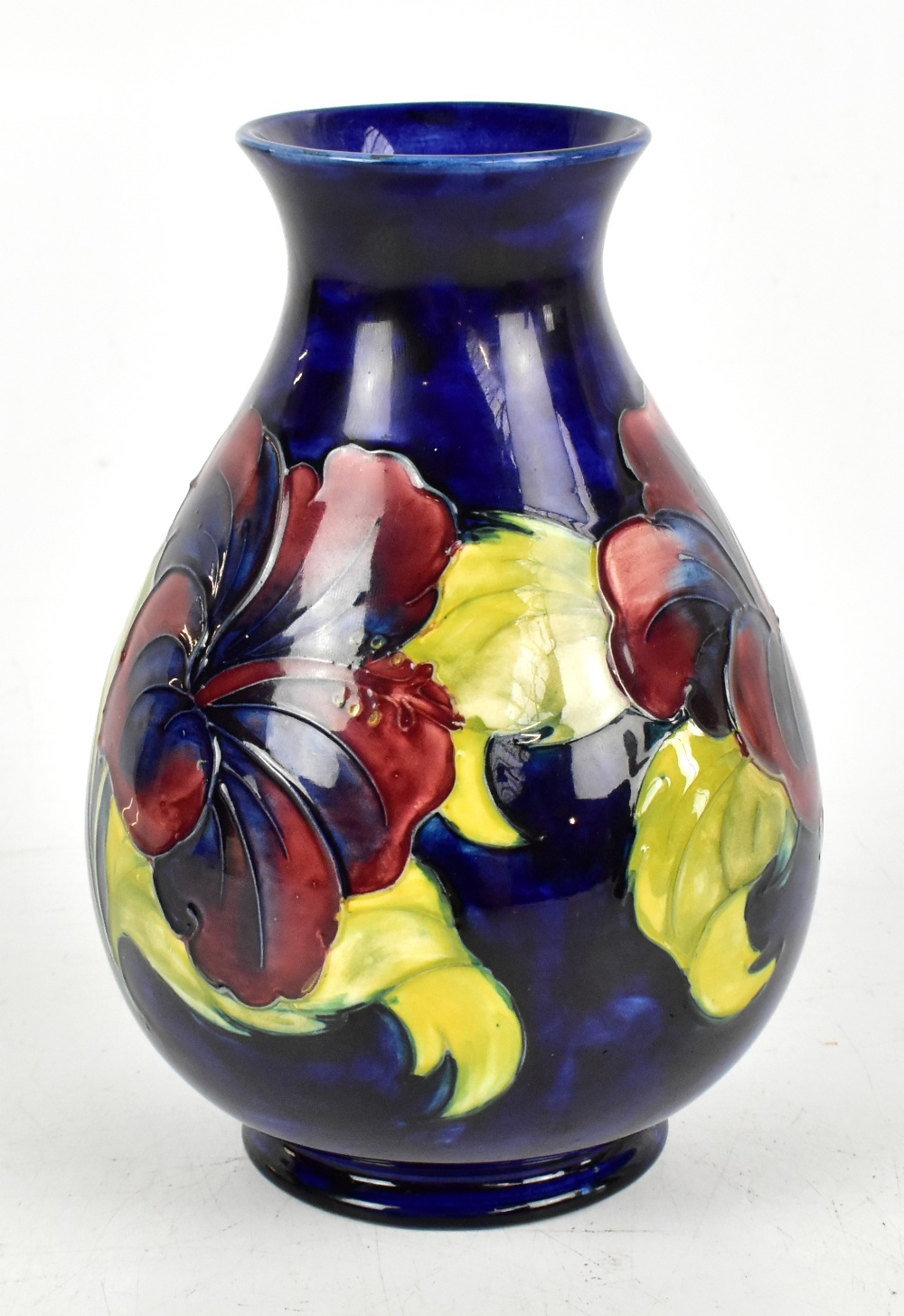 WALTER MOORCROFT; a baluster shaped vase decorated in the Hibiscus pattern on a blue ground,