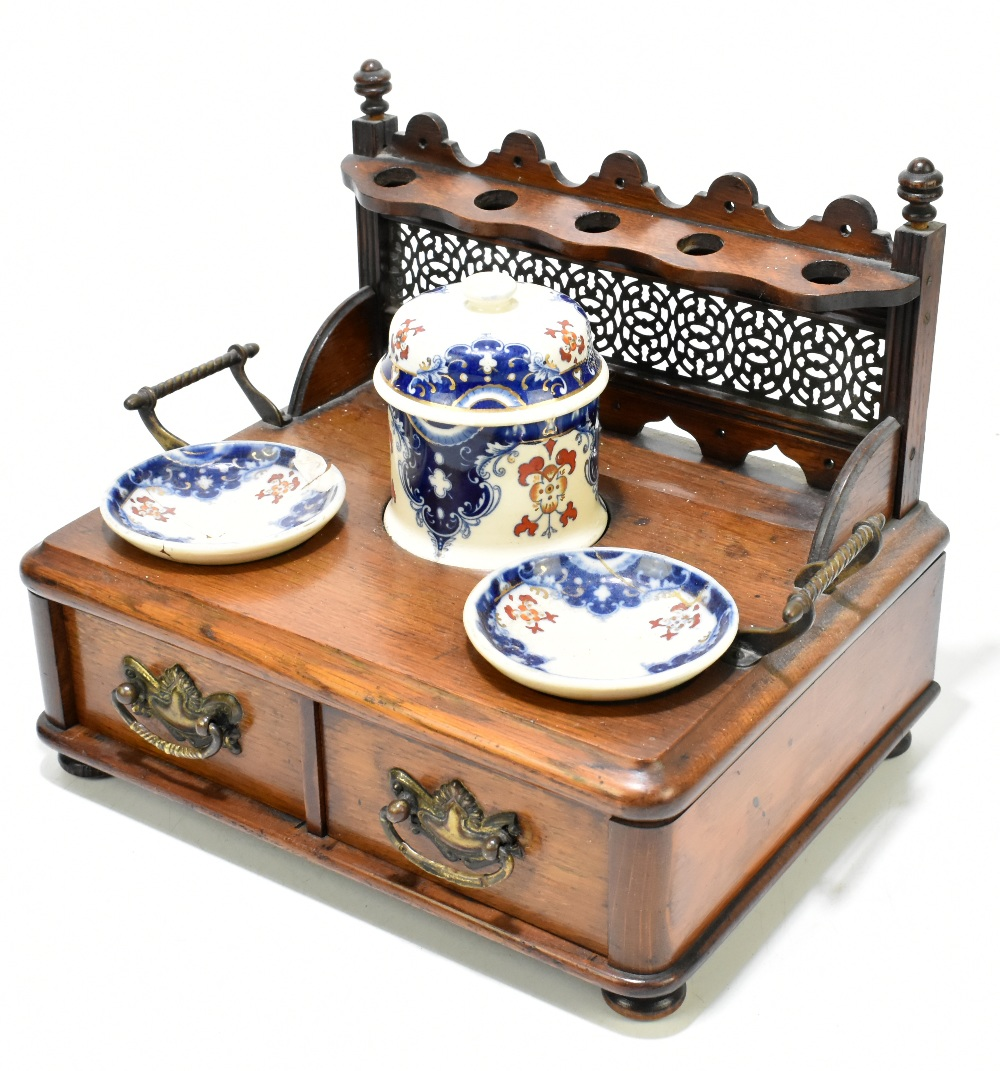 An early 20th century oak smoking stand with pierced pipe rack back above a ceramic lidded jar and