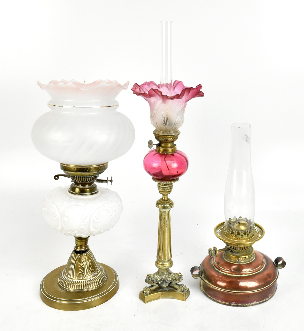 A 19th century brass oil lamp with cranberry glass reservoir raised on turned brass column