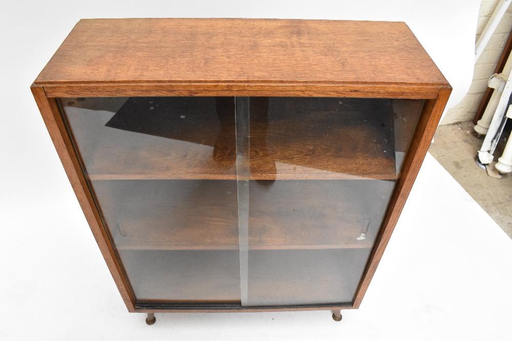 An oak bookcase with three sliding glass doors on castors, height 91cm, width 91.5cm, depth 22cm, - Image 6 of 6