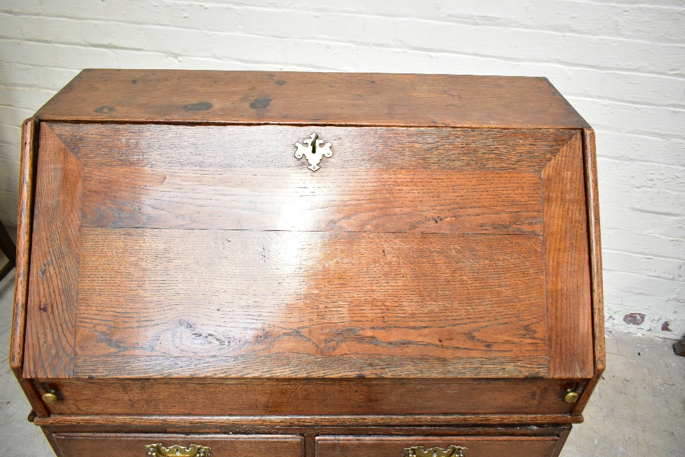 A George III oak bureau withfall-front enclosing a fitted interior with eight drawers and four - Image 3 of 6