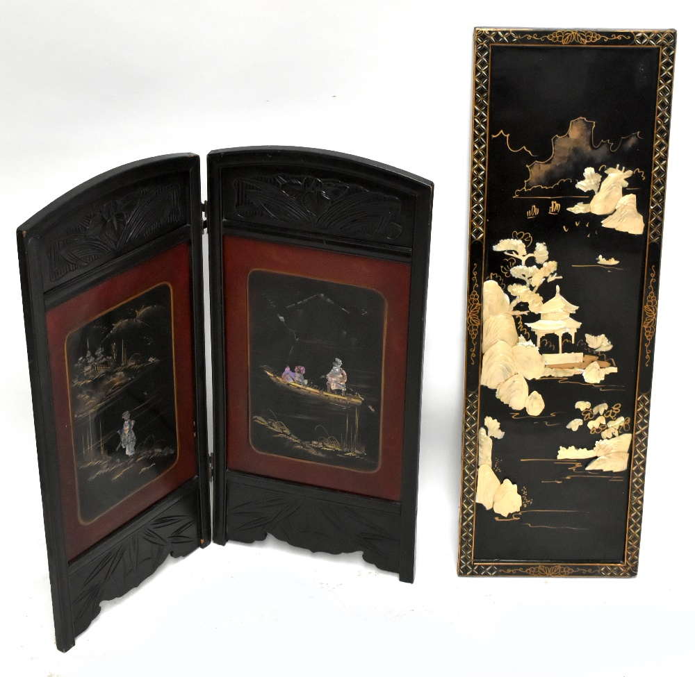 An early 20th century Chinese lacquered two division folding screen, the rectangular panels inlaid