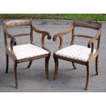 A pair of Regency carved mahogany elbow chairs with panelled cresting rails and rope twist bar