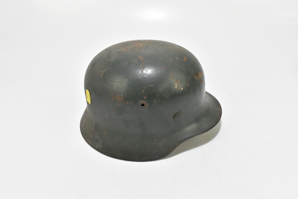 A German WWII Wehrmacht helmet bearing eagle and swastika decal, retaining leather liner and - Image 5 of 6