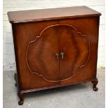 WARING & GILLOWS; a mahogany twin door cupboard raised on cabriole supports, length 100cm, depth