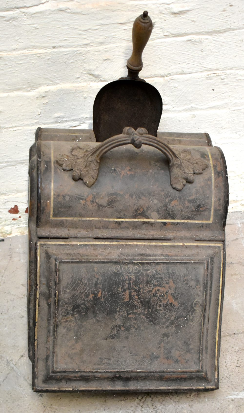 A Victorian toleware coal scuttle, of shaped arched form, with matched shovel, length 52cm (af).
