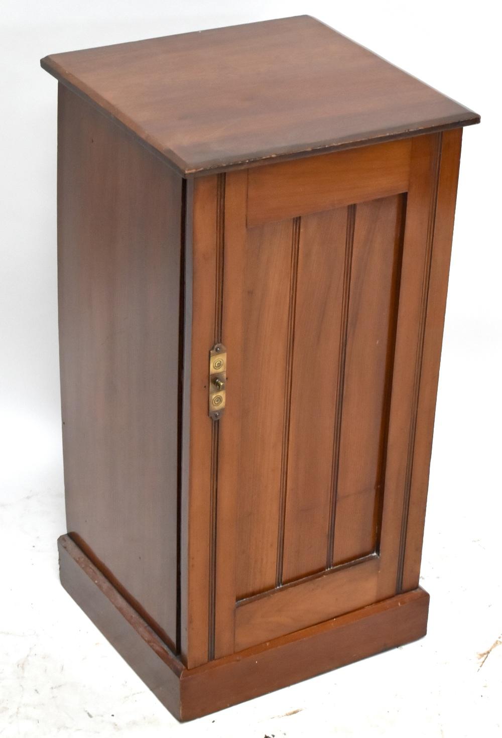 An Edwardian walnut pot cupboard, the single panel door enclosing a fixed shelf, raised on plinth