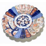 A large late 19th century Japanese Imari charger, of circular form with panelled detail depicting