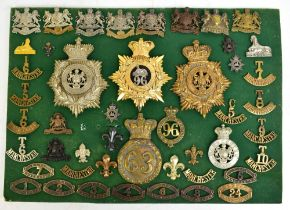 MANCHESTER REGIMENT; a good group of badges with three helmet/shako plates including a gilt metal
