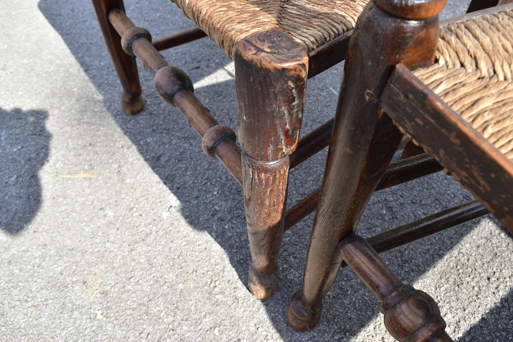 A matched set of six 19th century and later rush seated spindle back chairs, to include an elm - Image 4 of 4