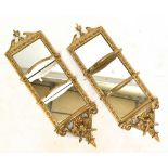 A pair of late 19th century gilt framed wall mirrors of rectangular form, with urn finials above