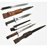 Four bayonets including two German and a socket example, two with scabbards and frogs, the two