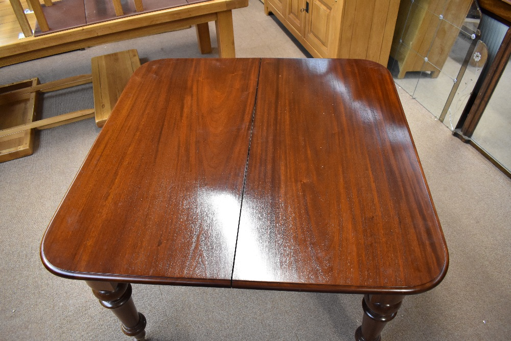 A Victorian mahogany wind-out extending dining table with two extra leaves on turned tapered - Image 2 of 5