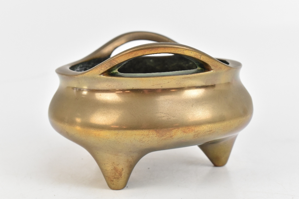 A Chinese bronze censer with raised pierced handles, three simple tapering supports and impressed - Image 4 of 7