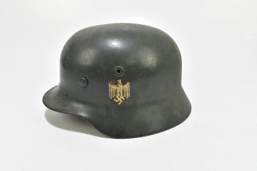 A German WWII Wehrmacht helmet bearing eagle and swastika decal, retaining leather liner and - Image 3 of 6