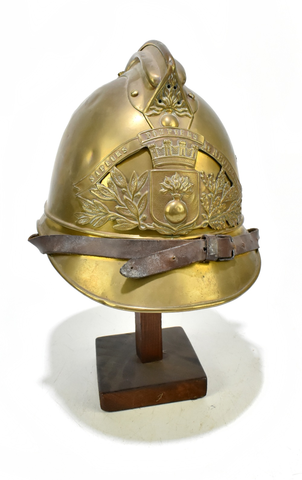 A French fireman's brass helmet with applied badge inscribed 'Sapeurs Pompiers De Neuille Le L.',