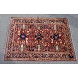 A Caucasian hand knotted wool rug decorated with geometric motifs against a red ground, 180 x 129cm.
