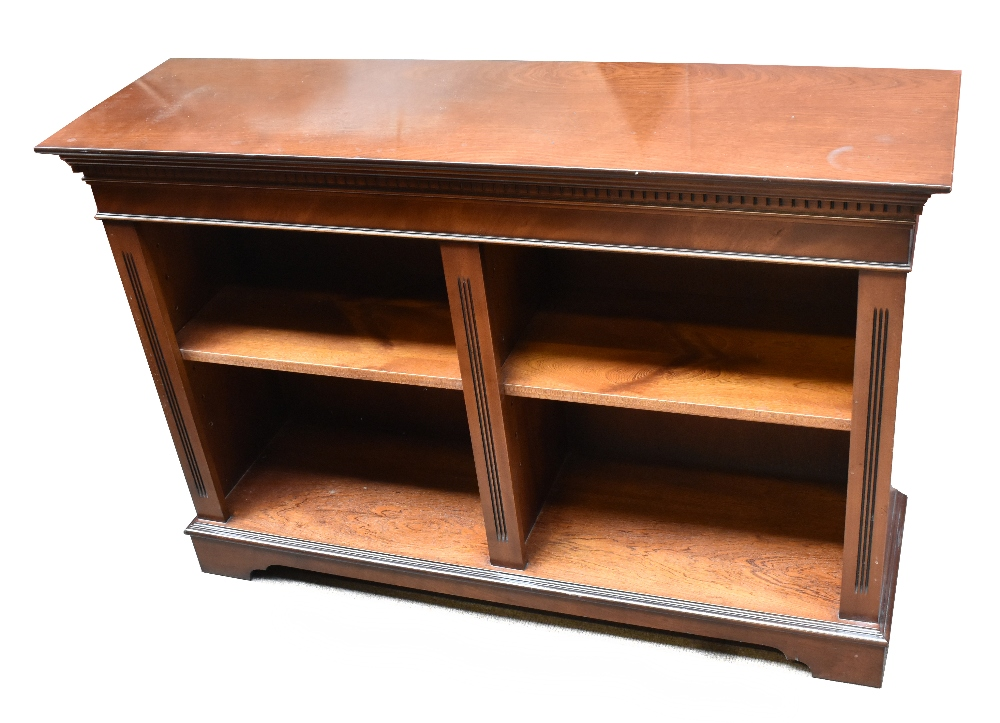 A reproduction mahogany veneered low bookcase, the twin open sections enclosing adjustable