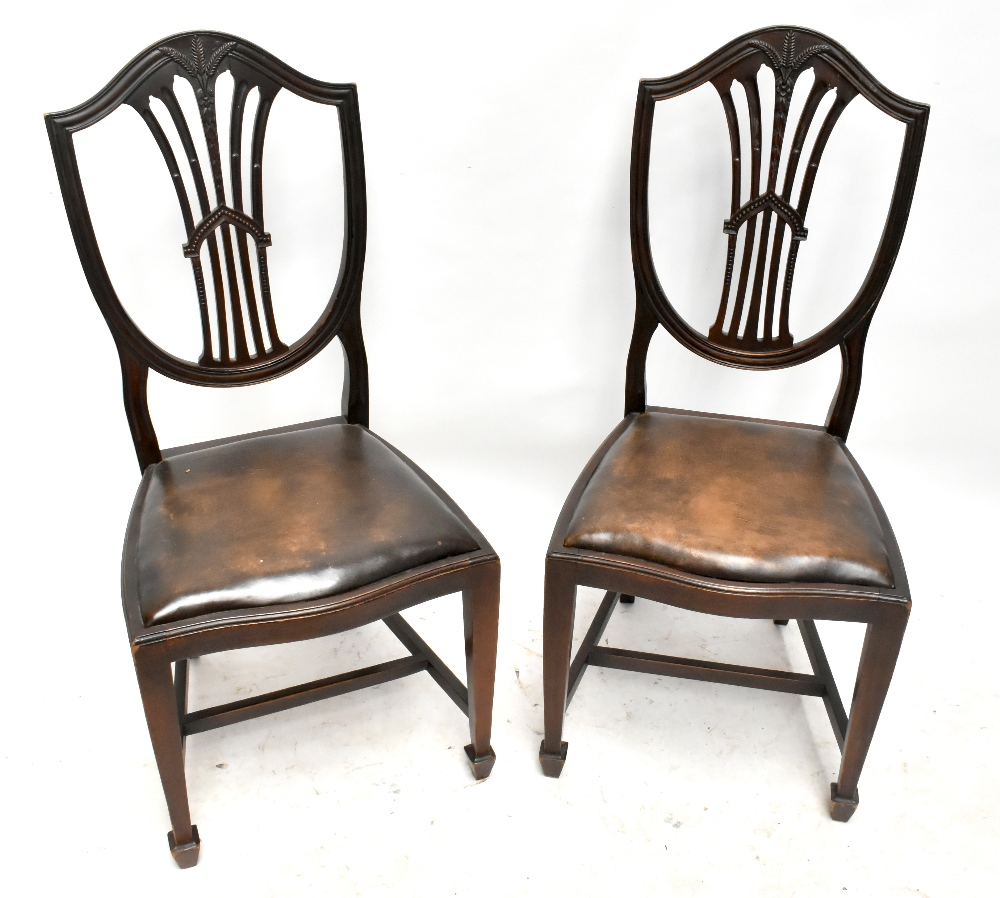 A set of four early 20th century mahogany shield back dining chairs with carved weatsheaf detail,