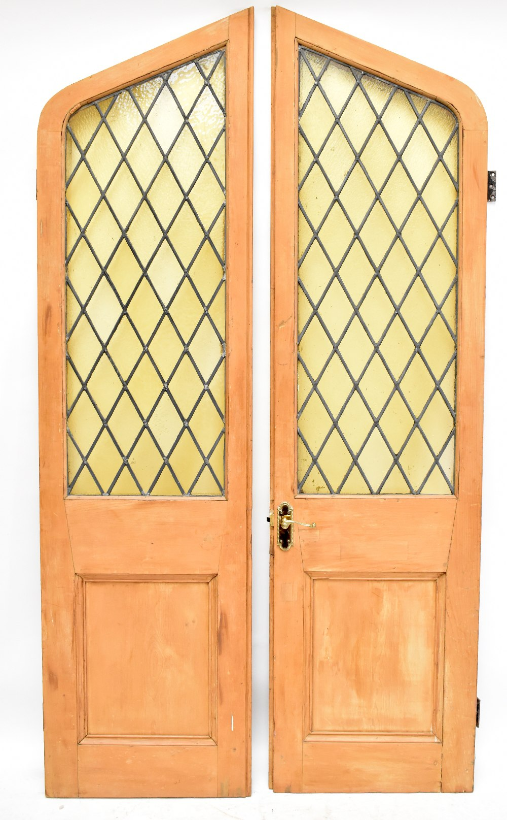An early 20thcentury large pair of carved pine arched doors, each inset with a leaded stained glass
