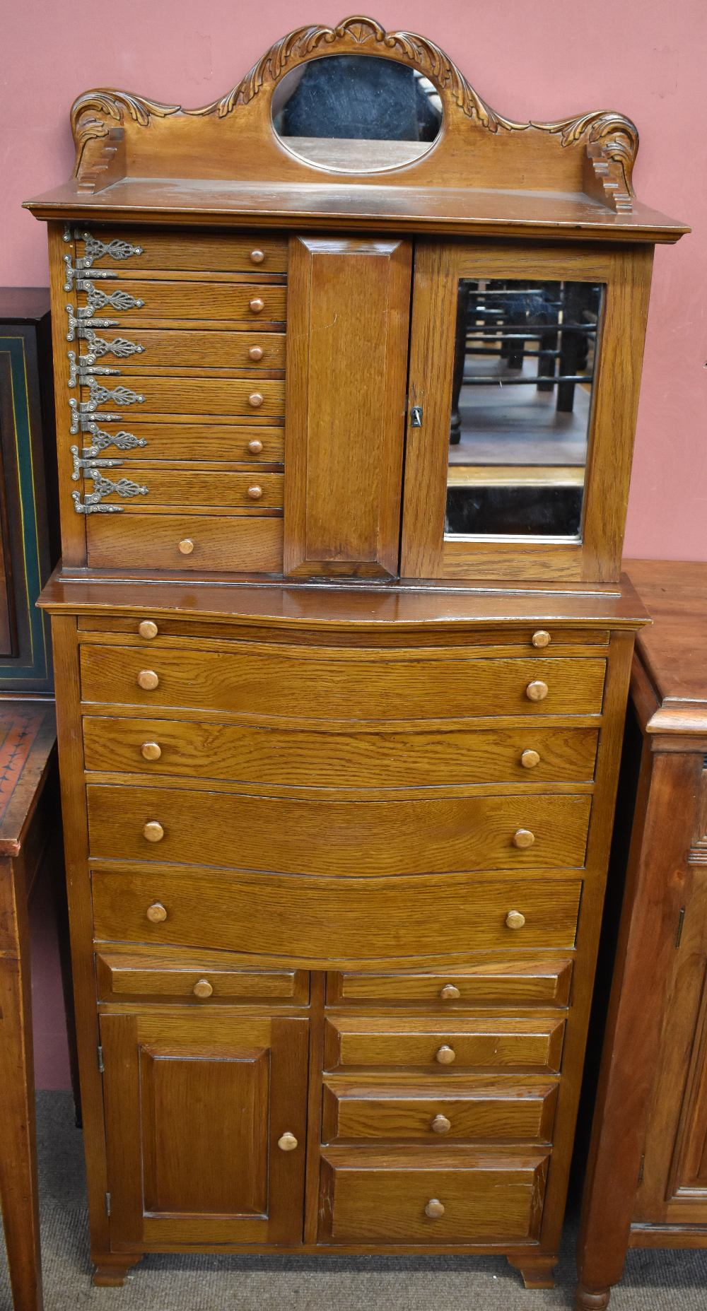 A modern Egyptian oak jewellery cabinet, with a mirrored cupboard door and seven small drawers