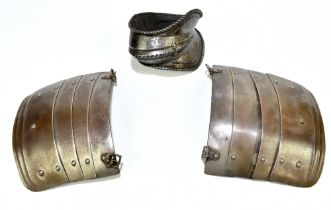 A pair of articulated steel pauldrons, 18.8 x 23.8cm, and an elbow guard (3). Provenance: The