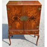 A Queen Anne style figured walnut cocktail cabinet with two doors enclosing two shelves above two
