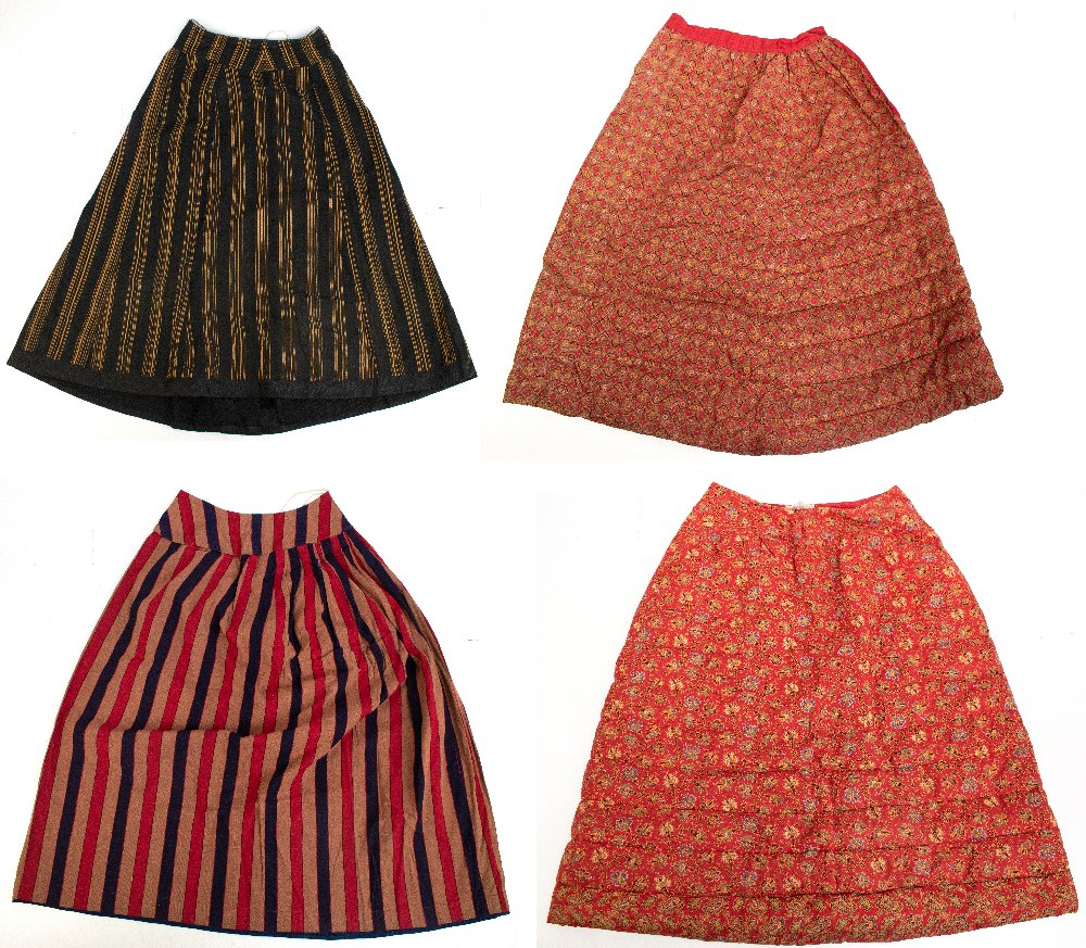 Two late Victorian quilted underskirts/winter petticoats, one decorated with a floral design against