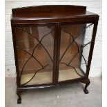 A 1930s walnut two door display cabinet with shaped astragal glazed doorsenclosing glass shelves on