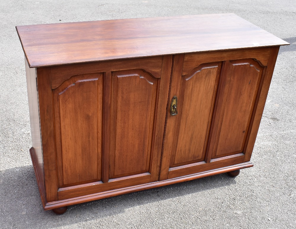 A linen cupboard with pair of panelled doors enclosing two slides, raised on bun feet, height