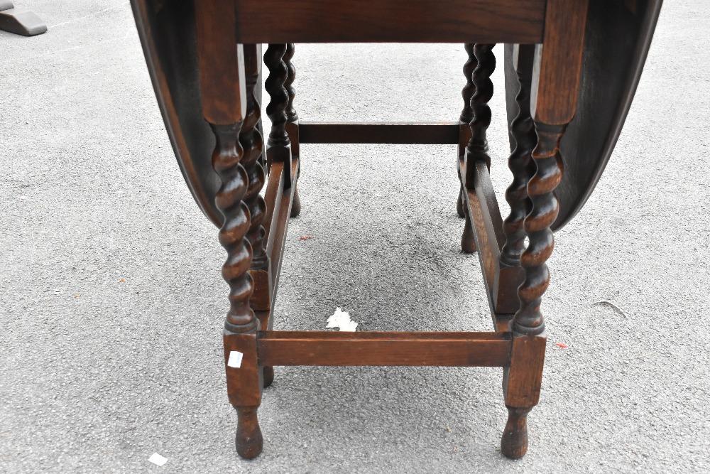 A 1920s carved oak gateleg table on barleytwist legs,height 72cm,width 107cm, with a similar set - Image 2 of 5
