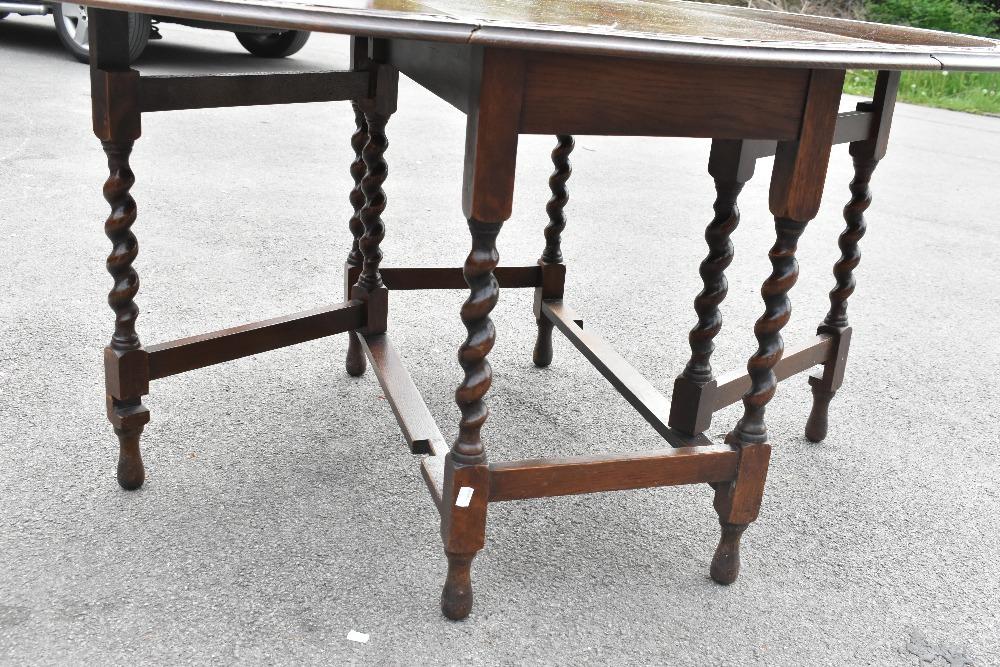 A 1920s carved oak gateleg table on barleytwist legs,height 72cm,width 107cm, with a similar set - Image 5 of 5