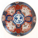 A Japanese Imari charger decorated with stylised floral detail and objects.